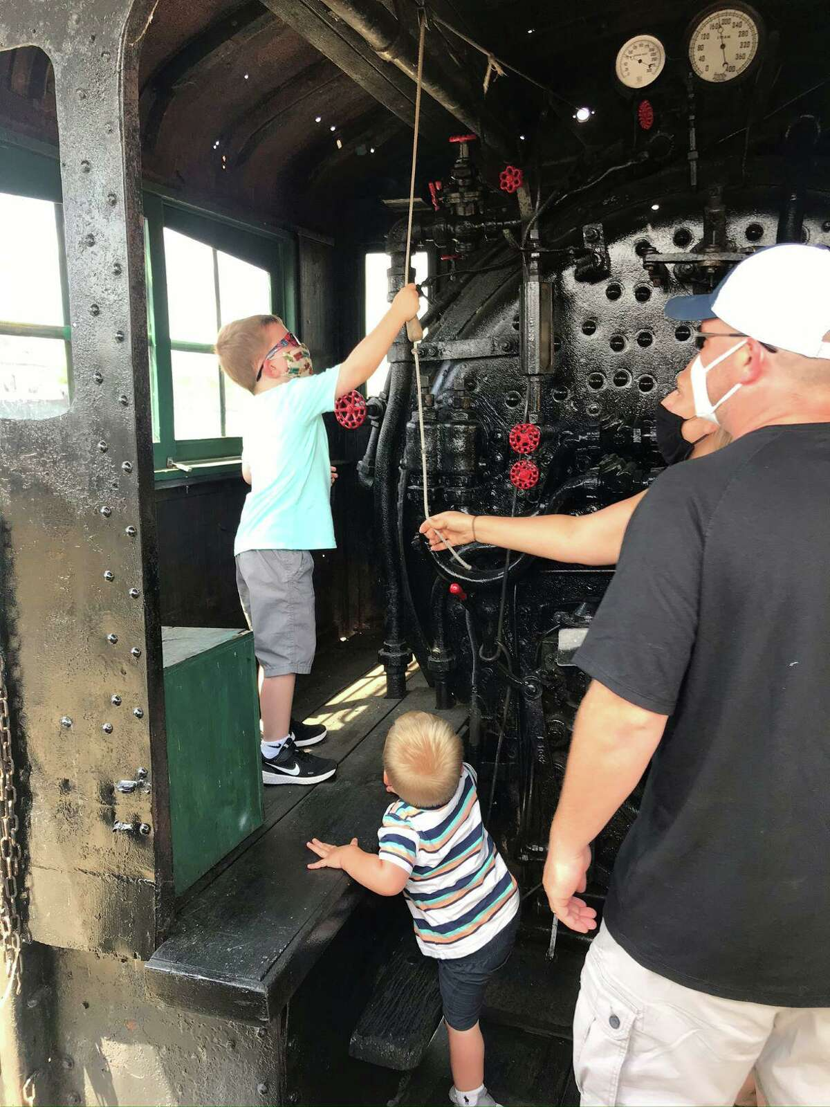 Visitors explore an exhibit at the Danbury Railway Museum. Jackson Pettigrew, 5, rings the 1907 steam locomotive bell while his parents, Dan and Michelle, and brother, Colton, 2, give moral support. The family was visiting from Poughkeepsie, N.Y.