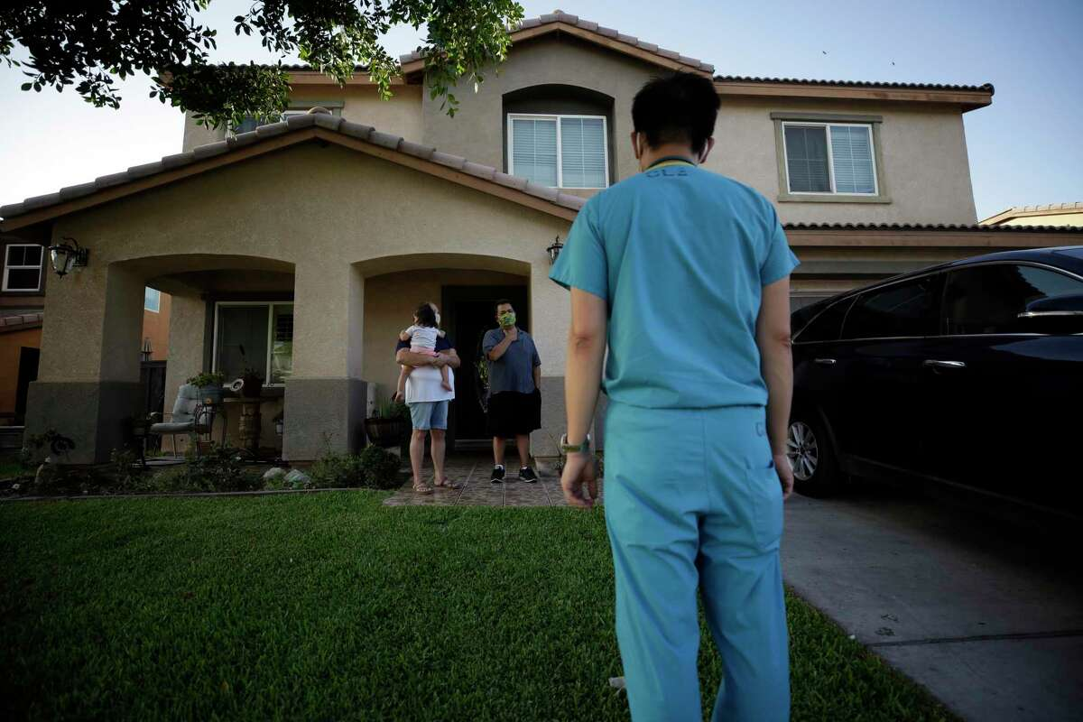 A doctor speaks with a family under quarantine in California in July. In addition to physical health, the COVID-19 pandemic has also stressed mental health. There are a number of steps Congress should take to improve access to care.
