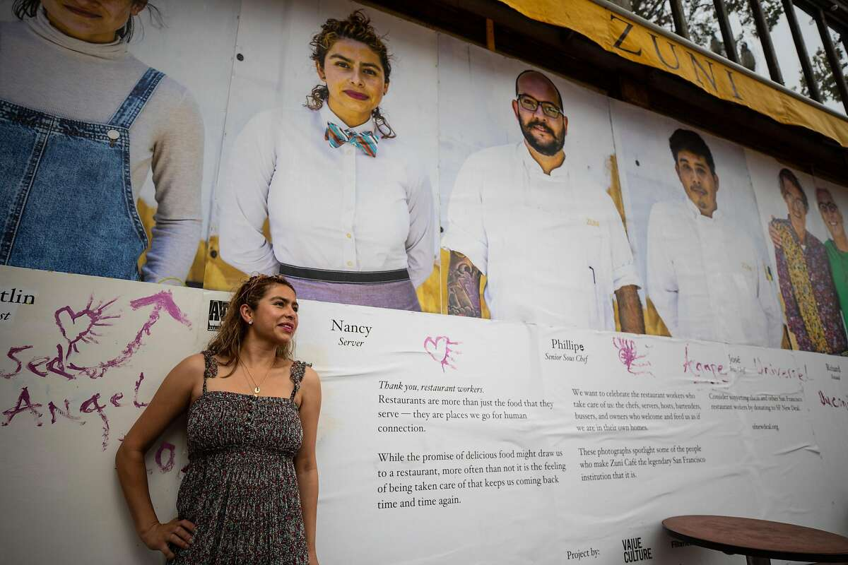 Nancy Martinez stands in front of a photo of her on the wall of Zuni Cafe where she was laid off when shelter in place started on Wednesday, August 5, 2020.