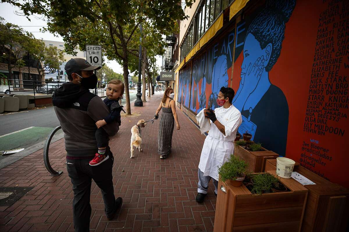 Nancy Martinez, center, walks her dog Mylo with her husband Matt Titman, left, and son Mylo on Wednesday, August 5, 2020. Martinez was laid off from Zuni Cafe when shelter in place started and her husband Matt Titman was laid off from Gary Danko.