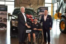 Leslie Doggett, left, and Jason Mosley, right, of Doggett Ford helped present Chase Cormier, a Houston Police Department officer, with a 2020 Ford F-150 Platinum.