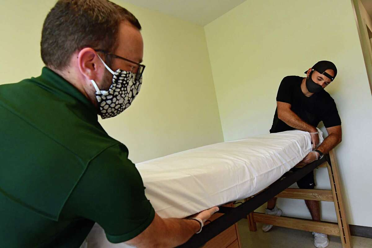 From left, Office of Community Living staff Andy Murphy and James Calechman make up the beds in a dorm room in Snyder Hall at Siena College on Thursday, July 30, 2020 in Loudonville, N.Y. Approximately 100 students will be moving onto campus August 3-5 to quarantine in Snyder Hall for at least 14 days before the start of classes on August 24. (Lori Van Buren/Times Union)