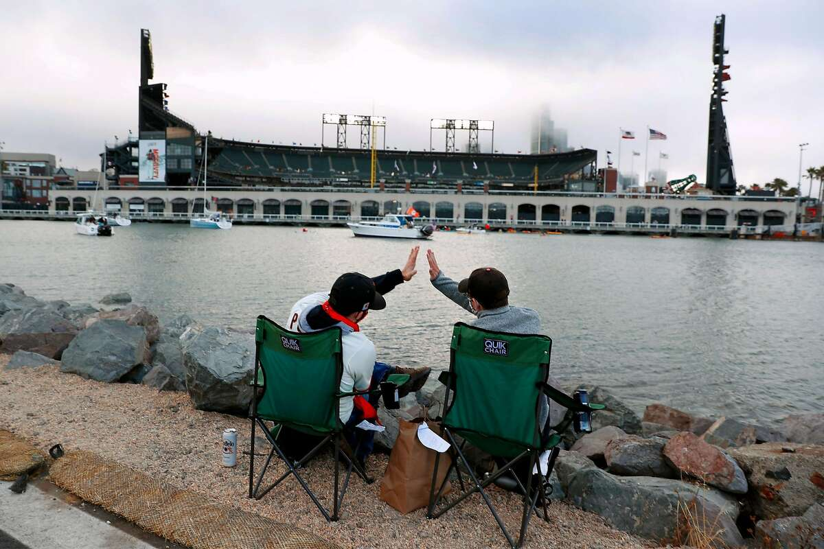 From their seats across McCovey Cove, San Francisco Giants' fans Armando Gonzalez and Dylan Gubrey high five after the Giants score in 1st inning of home opener at Oracle Park in San Francisco, Calif., on Tuesday, July 28, 2020.