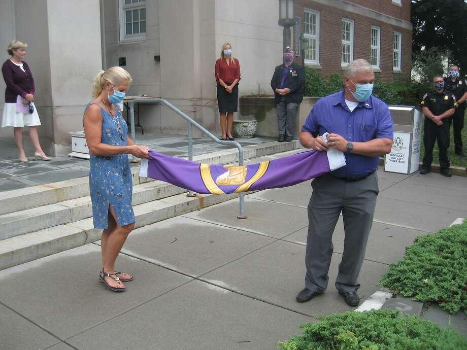 Lynn Zanderigo Florio and Torrington Public Works Director Raymond Drew prepare to raise the Purple Heart flag. Photo: John Torsiello / For Hearst Connecticut Media