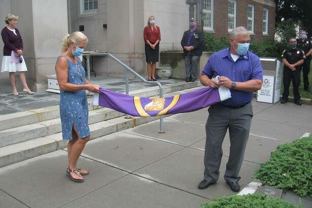 Lynn Zanderigo Florio and Torrington Public Works Director Raymond Drew prepare to raise the Purple Heart flag.