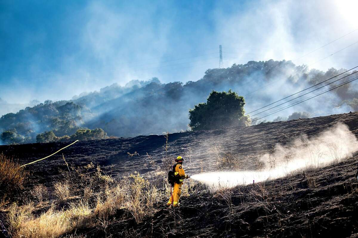 A firefighter sprays water while mopping up after the Calaveras Fire on Thursday, Aug. 6, 2020, near Sunol, Calif. Firefighters were investigating the incident, located at a San Francisco Public Utilities Commission facility, as a crime scene.