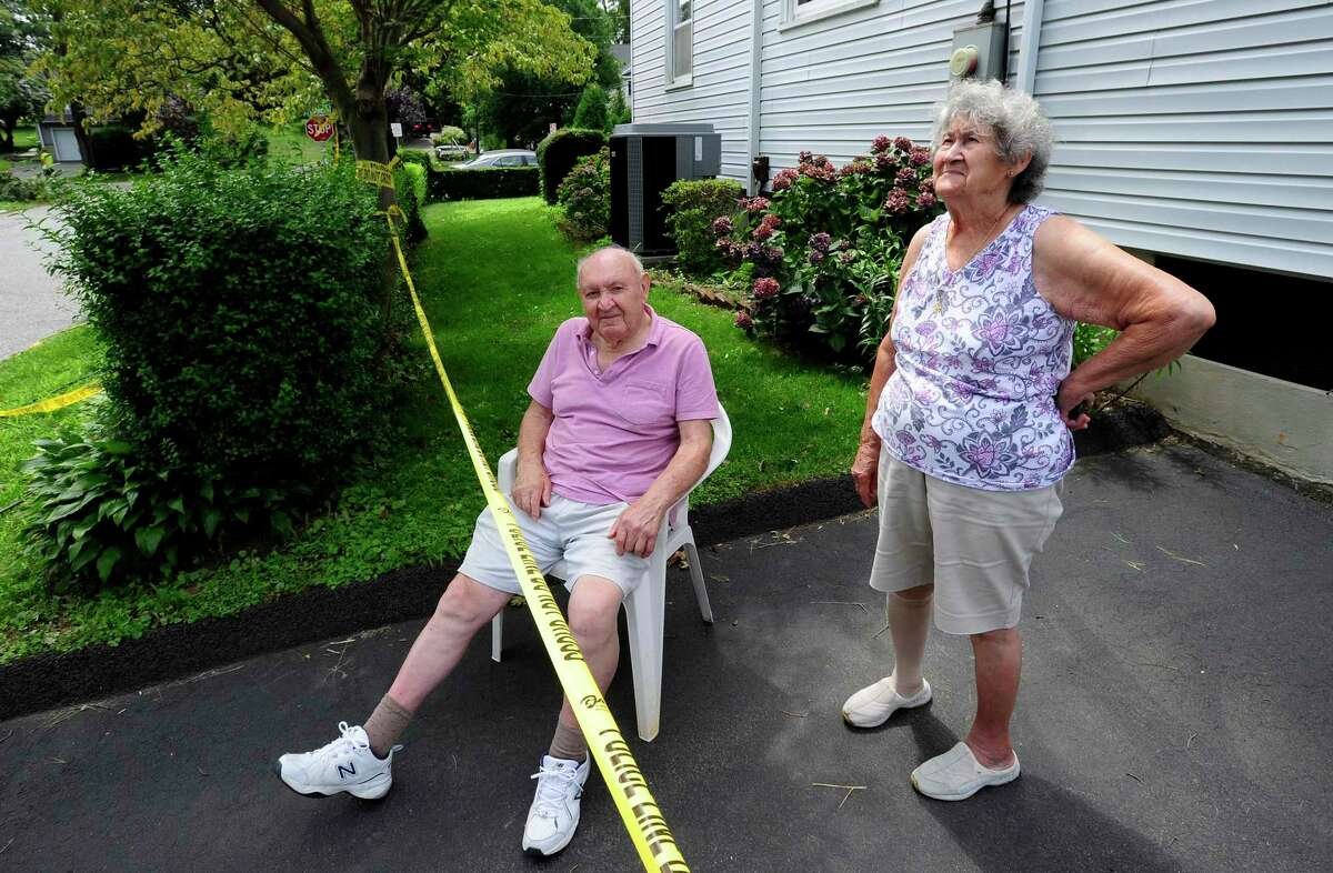 Sam Gentile and his wife Teresa watch as a crew from Asplundh Tree Expert Companyout of New Hampshire work on August 7, 2020 to cut up a fallen tree that has blocked his and his neighbors driveways on Frisbie Street in Stamford, Connecticut.