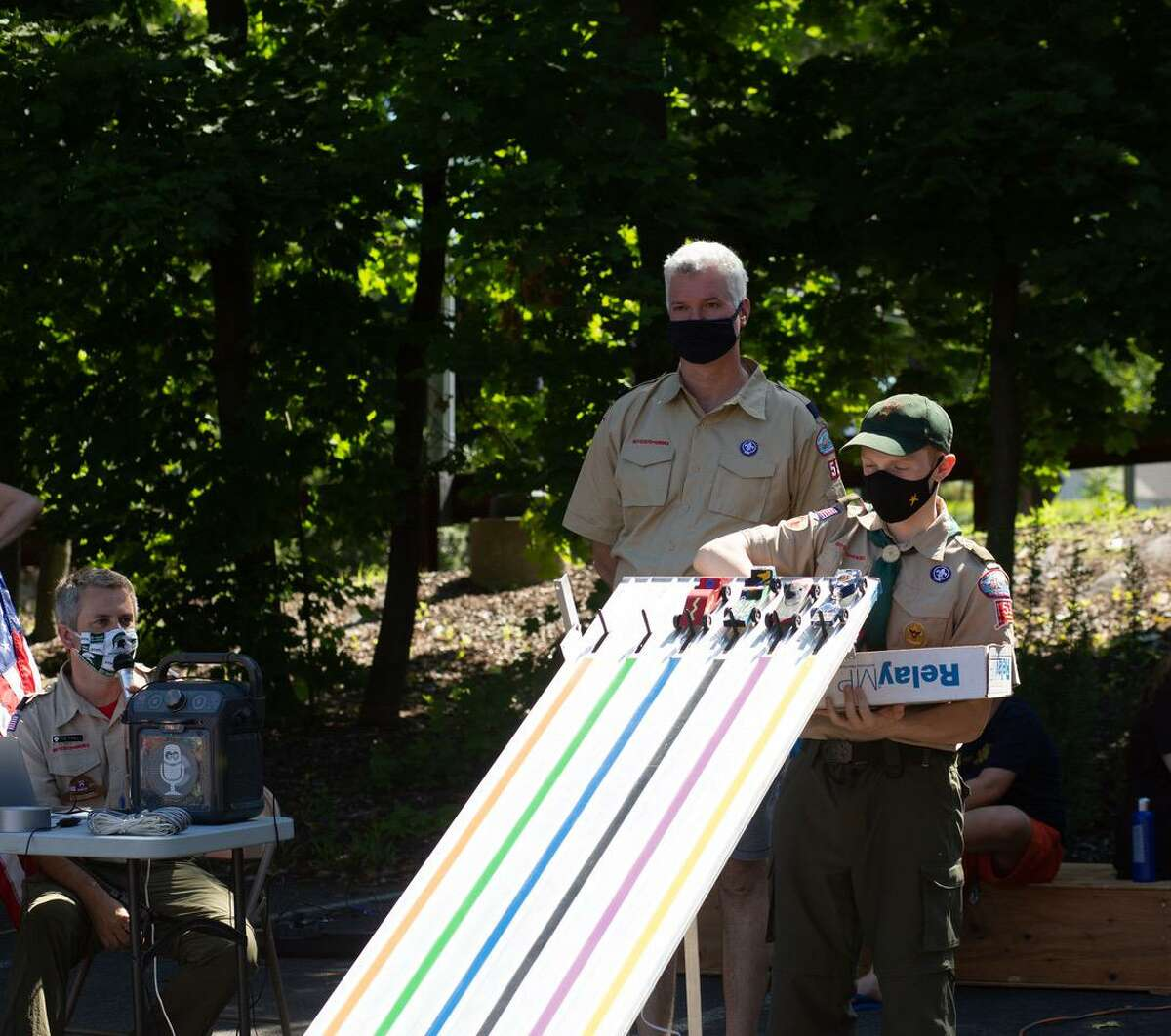 Rob Farley, seated left, Kevin Reade and Will Laird, den chief at the Pack 55 & 56, at the Pinewood Derby.