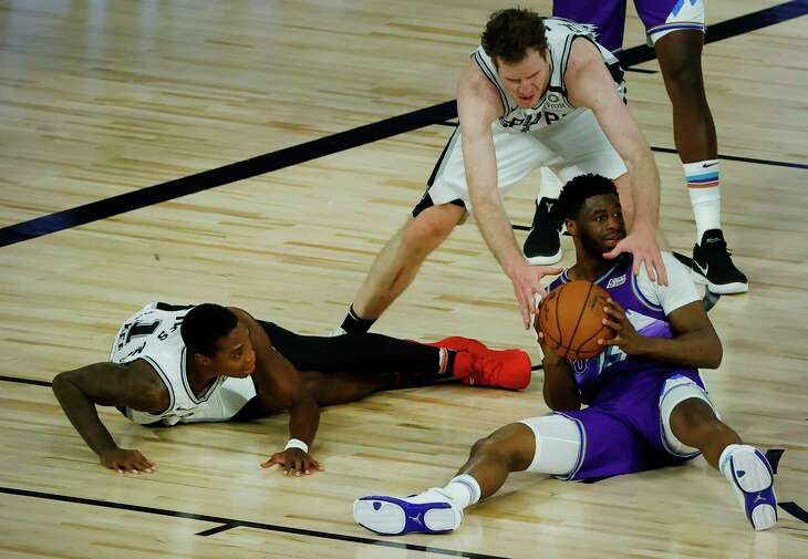 San Antonio Spurs' Jakob Poeltl, top right, reaches to steal the ball from Utah Jazz's Tony Bradley #13 of the Utah Jazz as San Antonio Spurs' Lonnie Walker IV looks on during the first half of an NBA basketball game Friday, Aug. 7, 2020, in Lake Buena Vista, Fla. (Kevin C. Cox/Pool Photo via AP)