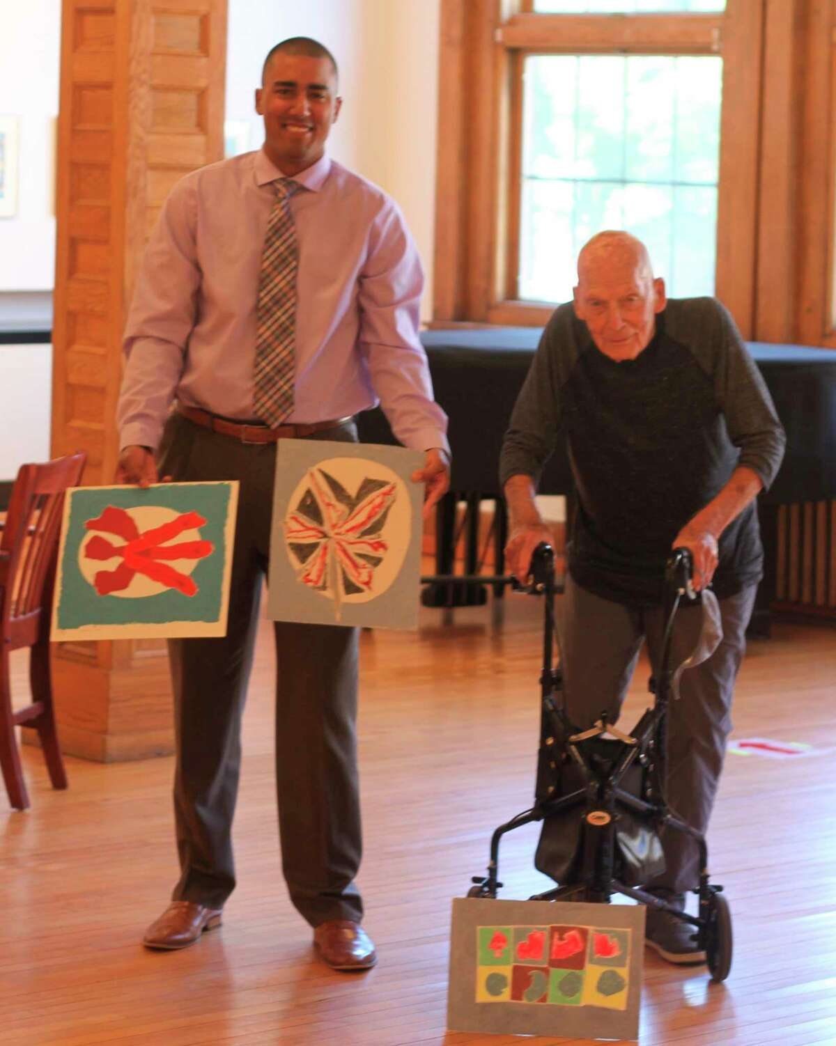 Executive director of the Ramsdell Regional Center for the Arts, Xavier Verna (left) stands with Manistee native and nationally renowned artist Leslie Laskey and three paintings Laskey donated to the RRCA in August 2020. (Kyle Kotecki/News Advocate)