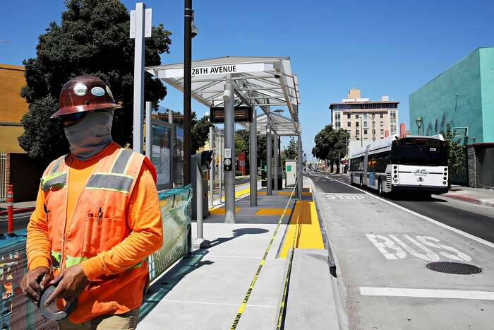 Lauro Gutierrez, an employee with Golden Bay Fence Plus Iron Works, Stockton, works with two colleagues to wrap plastic on the railing at the new BART bus platform at 28th Ave. and International Blvd. on Friday, August 7, 2020, in Oakland, Calif. The bus line opens Sunday after decades of planning and debate, followed by a long construction period. It will connect Oakland's flatland neighborhoods to jobs in the downtown core.