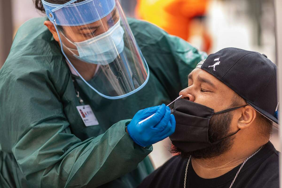 Alonso Reyes, right, gets tested at a COVID-19 testing area that was set up at the 24th Street Mission Station by BART and UCSF on Wednesday, Aug. 5, 2020. The testing program aims to help get more members of the Latino community tested.