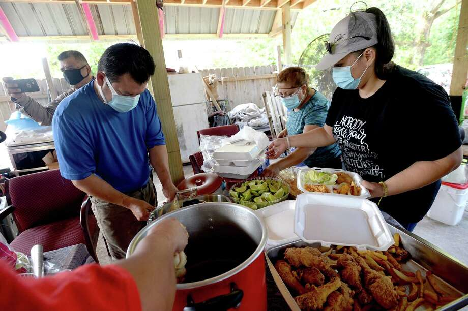 From left, Roy Herrera, Lupita Rodriguez and Adriana Vasquez join in the cooking and plating as they gather for a fundraisinng food sale for Jaerson Alvarez and Wilmer Alexi Rodriguez, both 18, who drowned as they tried to help a man and his daughter that needed help while swimming in the Trinity River August 2. Photo taken Friday, August 7, 2020 Kim Brent/The Enterprise Photo: Kim Brent / Kim Brent/The Enterprise / BEN