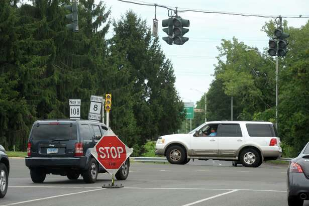 With traffic lights out, temporary stop signs remained in place Friday afternoon at the intersection where Nichols Avenue and Penny Lane meet with the northbound onramp to Route 8, in Trumbull, Conn. Aug. 7, 2020.