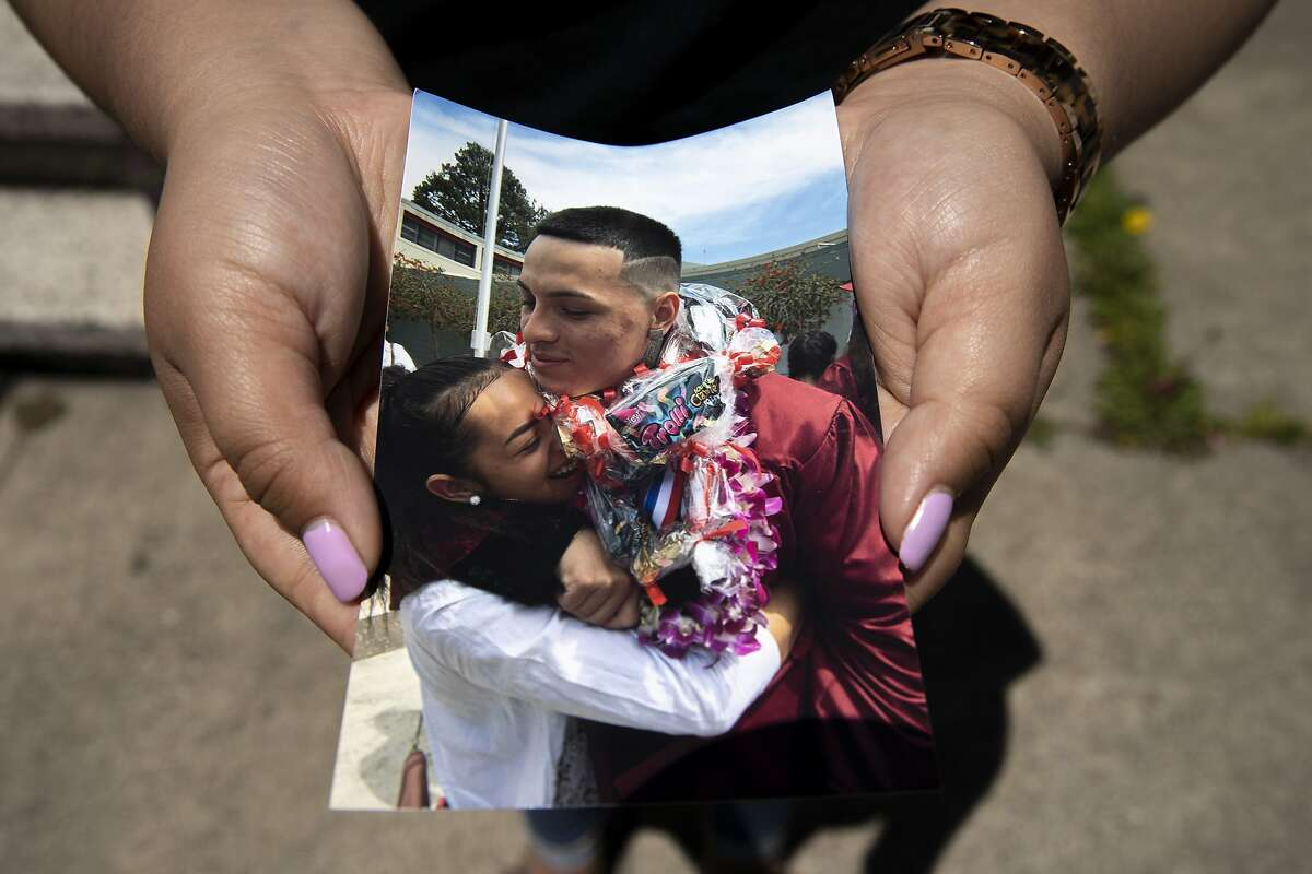 """Ashley Monterrosa holds a photo of her hugging her brother Sean Monterrosa at SeanÍs 2016 graduation, Thursday, June 4, 2020, in San Francisco, Calif. Her brother Sean Monterrosa, 22, was fatally shot by Vallejo police. He was kneeling outside a Walgreens and not carrying a firearm when an officer opened fire """" sending five bullets through his own windshield. Monterrosa, of San Francisco died after the shooting at around 12:30 a.m. Tuesday, but police did not tell the public the man was killed """" or disclose the circumstances of the shooting """" until Wednesday at a news conference outside City Hall, a day after calling in 50 troops from the National Guard to help control protests and rioting sparked by the Minnesota police killing of George Floyd."""