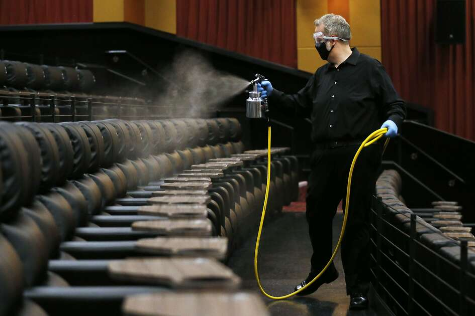 Cinemark West general manager Lindsey Hearn sprays disinfectant on seats in an auditorium the morning before the theater's June 19 reopening. (Vernon Bryant/The Dallas Morning News/TNS)