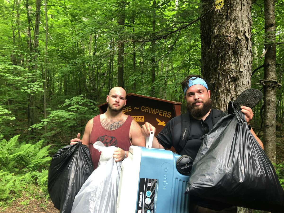 With help from other hikers, Shaun Hazlitt of Johnsburg, left, and Jacob Gaechter of North Creek hauled garbage off Crane Mountain in June.