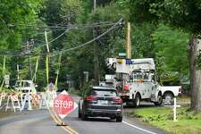 An Eversource truck passes downed utility lines where traffic has been reduced to one lane at the intersection of Lake and North Maple Avenues on August 7, 2020 in Greenwich, Connecticut.