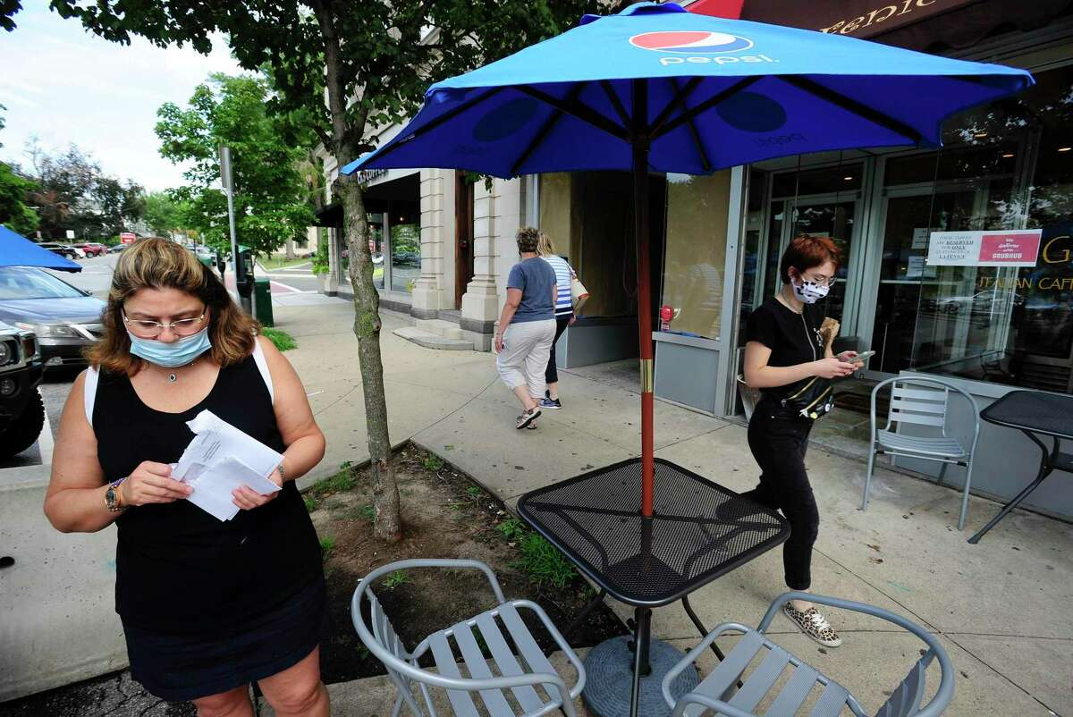 At left, Simona Silvestri, owner of La Fenice Gelateria checks her mail as residents stroll down Greenwich Avenue on August 7, 2020 in Greenwich, Connecticut.