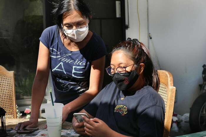 Russlyn Nicolas (left) talks with her daughter Samantha Marucut (right), on the patio at home on Tuesday, Aug. 4, 2020, in Antioch, Calif. Sophomore Samantha, 19 years old, used to babysit while attending college but lost her job since the pandemic and is waiting when school starts.