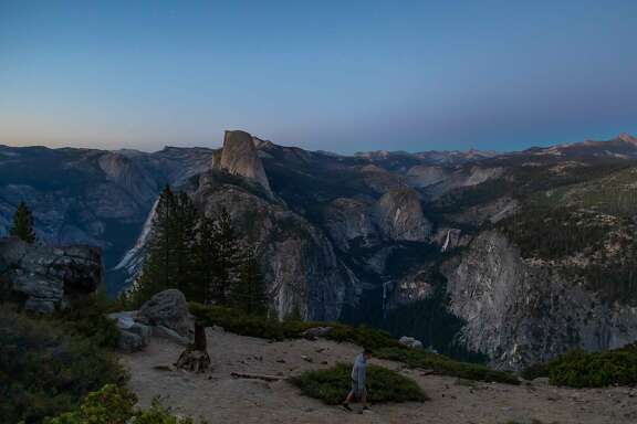 Dusk falls over Half Dome (C L) and Nevada Fall (C R) as a visitor walks at Glacier Point in the Yosemite National Park, California on July 07, 2020. - After closing for 2� months because of the coronavirus pandemic, the wildlife is taking over of areas used by the public. The park is open with limited services and facilities to those with day-use reservations, reservations for in-park lodging or camping, and wilderness or Half Dome permits. (Photo by Apu GOMES / AFP) (Photo by APU GOMES/AFP via Getty Images)