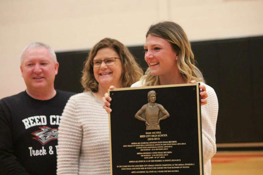 Sami Michell (right), standing with her dad Brent and mother Vikki, also her Reed City track coaches, accepted a plaque earlier this year honoring her high school sports achievements. The plaque is displayedat the football field/track facility. (Pioneer file photo)