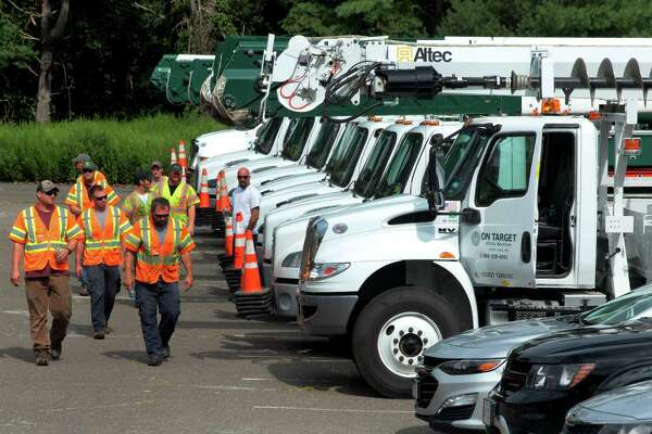 Crews from On Target Utility Service in Maine stage at Christ the King Catholic Church in Trumbull, Conn., on Friday Aug. 7, 2020. Many homes throughout the region were still left without power since tropical storm Isaias hit the area on Tuesday.