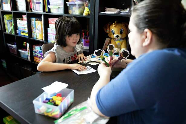 Angela Bickford helps her daughter, Tenley, through a lesson in their home in Cypress, August 6, 2020. Tenley is a life skills student and also lives with epilepsy.