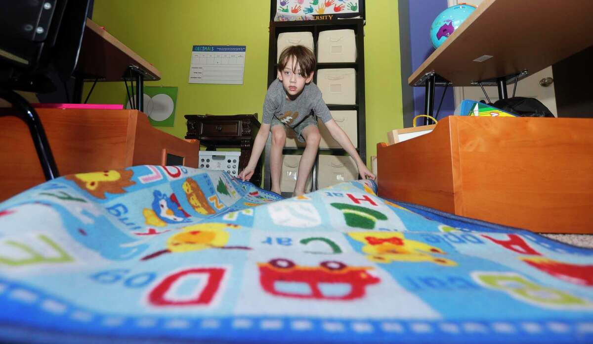 Fourth grader Owen Rakunas helps spread out a carpet with the alphabet displayed on it as he and his family prepare at-home learning spaces in their home, Friday, Aug. 7, 2020, in Cypress. Owen's parents opted to begin the school year with at-home instruction for their two children after Cy-Fair ISD pushed the school start date for students from Aug. 24 to Sept. 8, to give additional time for district officials to observe COVID-19 conditions in Harris County.