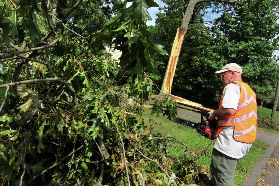 Pat Notarnicola works to remove a downed tree in the front yard at his home off of Tanglewood Road in Trumbull, Conn., on Friday Aug. 7, 2020.
