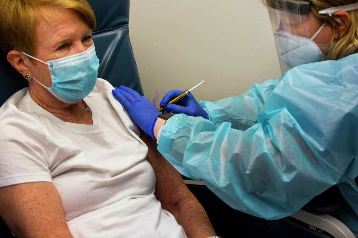 Linda Lamberth, left, 66, participates in a double blind trial which entails getting an experimental vaccine for COVID-19 at the Baylor College of Medicine on Friday, Aug. 7, 2020, in Houston. Lamberth gets the vaccine from Annette Nagel, a research nurse Baylor College of Medicine.
