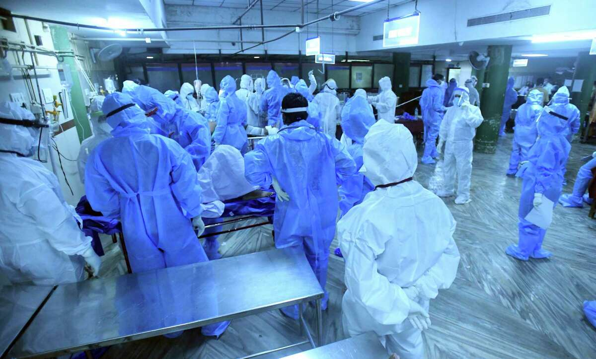 Medical personnel in personal protective wear stand as people injured after an Air India Express flight skidded off a runway while landing at the Kozhikode airport, are treated at the Medical College Hospital in Kozhikode, Kerala state, India, Friday, Aug. 7, 2020. (AP Photo/Shijith Sreedhar)