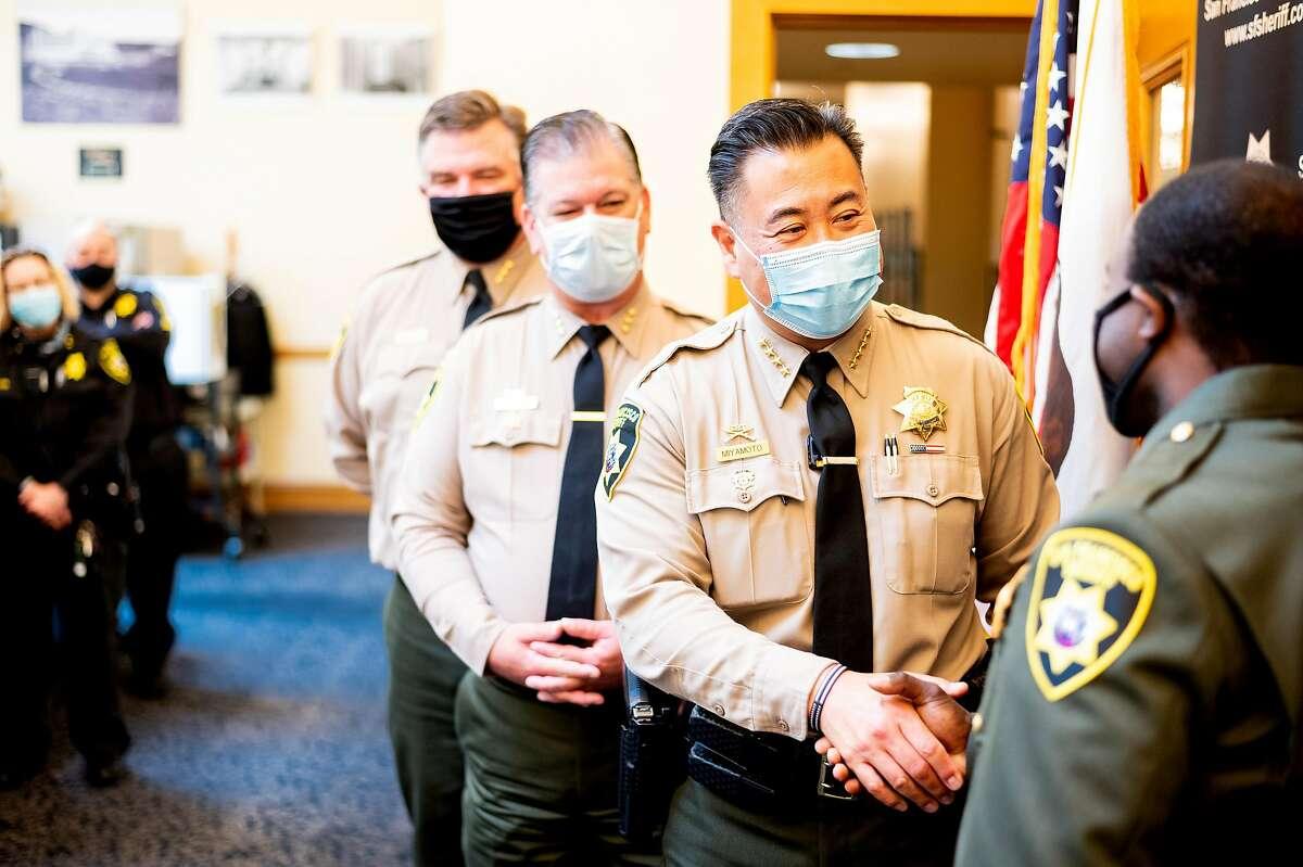 San Francisco Sheriff Paul Miyamoto congratulates a new sheriff's deputy during a pinning ceremony on Friday, Aug. 7, 2020, at San Francisco City Hall.
