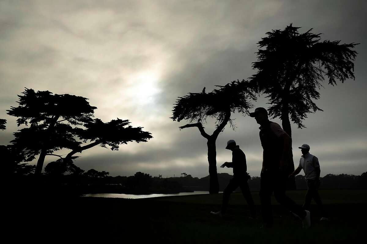 Jordan Spieth, Justin Rose and Dustin Johnson leave the 18th green at the end of their 2nd round of PGA Championship at TPC Harding Park in San Francisco, Calif., on Friday, August 7, 2020.