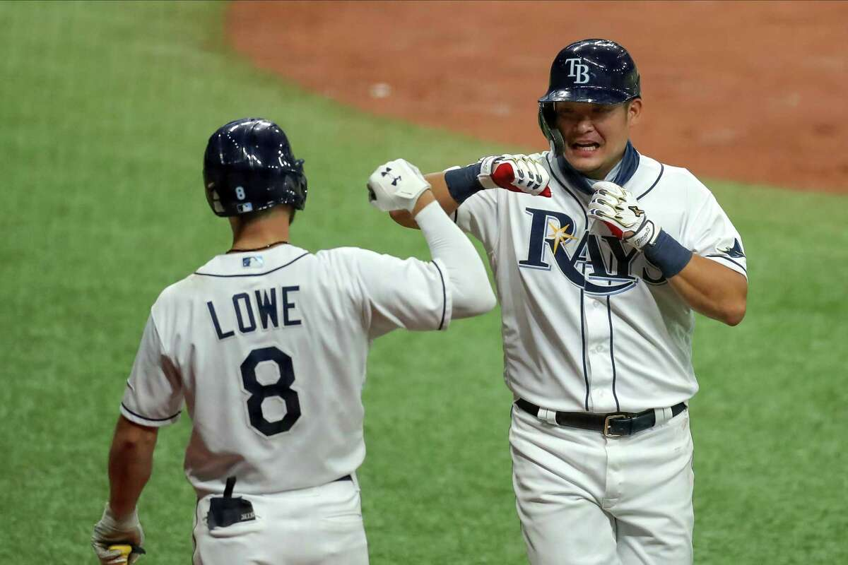 ST. PETERSBURG, FL - AUGUST 7: Yoshitomo Tsutsugo #25 of the Tampa Bay Rays, right, is congratulated by Brandon Lowe #8 after scoring against the New York Yankees in the eighth inning of a baseball game at Tropicana Field on August 7, 2020 in St. Petersburg, Florida. (Photo by Mike Carlson/Getty Images)