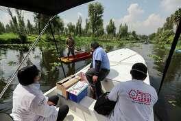 Trabajadores de la salud recorren en un bote uno de los canales de la zona de cultivos de Xochimilco, en el sur de la ciudad de México, el miércoles 5 de agosto de 2020, para recolectar muestras de pruebas diagnósticas de COVID-19.