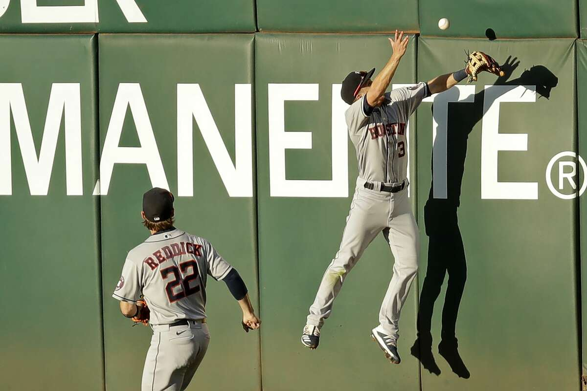 Houston Astros' Myles Straw, right, and Josh Reddick (22) can't make the catch on a ball hit for a double by Oakland Athletics' Matt Chapman in the fourth inning of a baseball game Friday, Aug. 7, 2020, in Oakland, Calif. (AP Photo/Ben Margot)