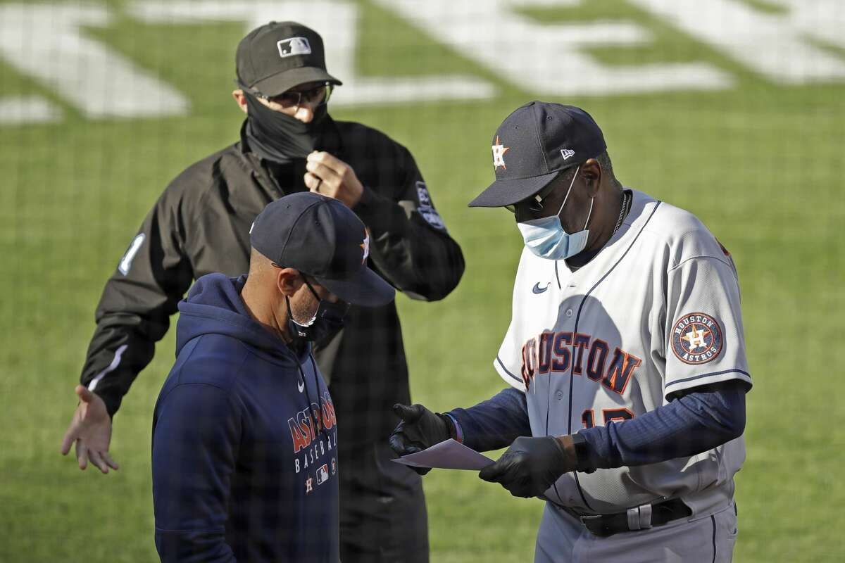 Houston Astros manager Dusty Baker Jr., right, goes over a lineup card with an umpire prior to the baseball game against the Oakland Athletics Friday, Aug. 7, 2020, in Oakland, Calif. (AP Photo/Ben Margot)