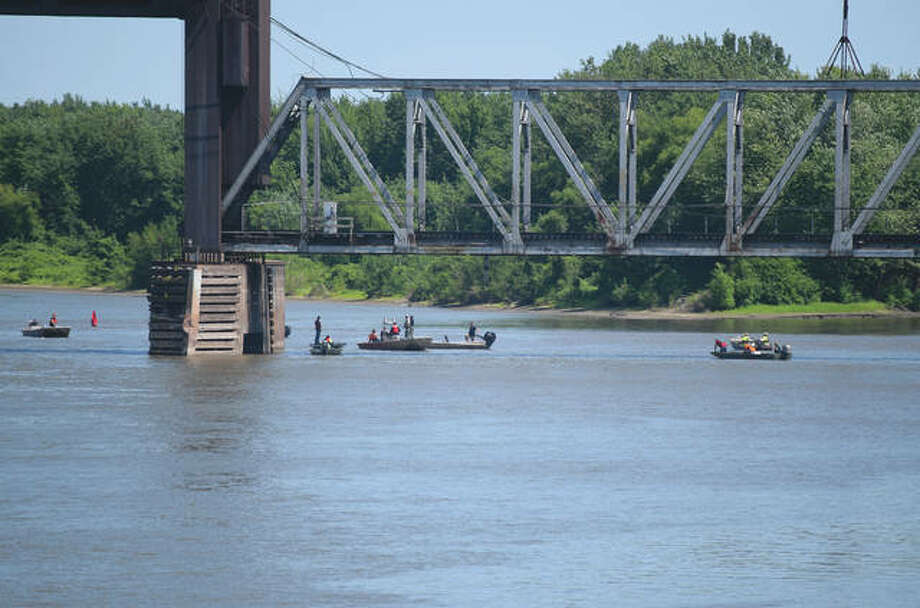 Rescue teams search Friday in the area of the Illinois River where two boys last were seen after being pulled into the river Thursday night.