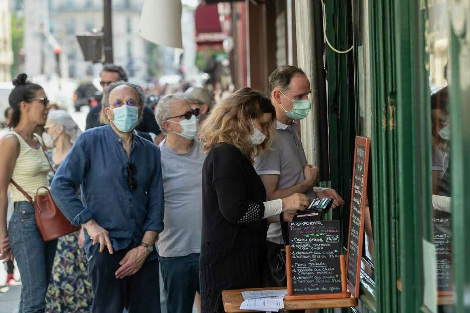 People wear masks to help curb the spread of the coronavirus line up to buy an ice-cream in Paris, Thursday May 21, 2020 as France gradually lifts its Covid-19 lockdown.