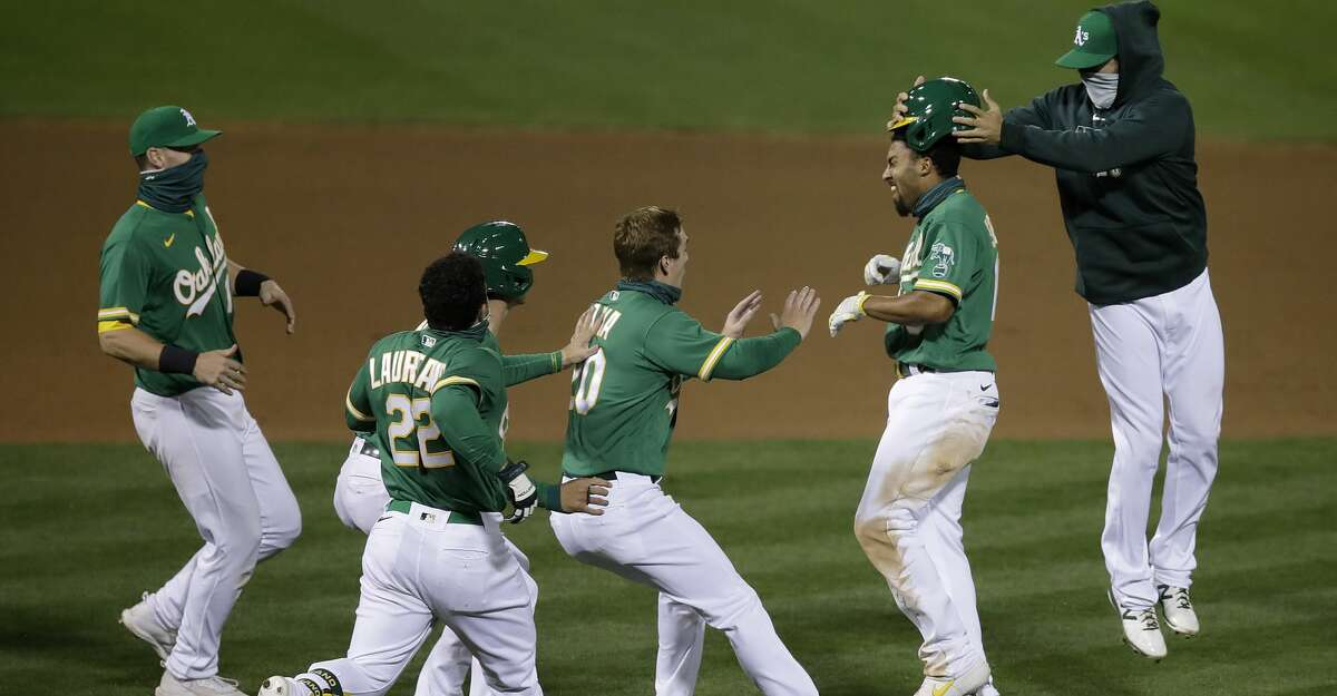 Oakland Athletics' Marcus Semien, second from right, celebrates with teammates after driving in the game winning run in the 13th inning of a baseball game against the Houston Astros Friday, Aug. 7, 2020, in Oakland, Calif.