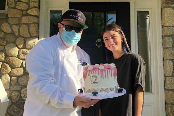 TikTok star Charli D'Amelio of Norwalk poses with her cake and with Sky Mercede of Forever Sweet Bakery.