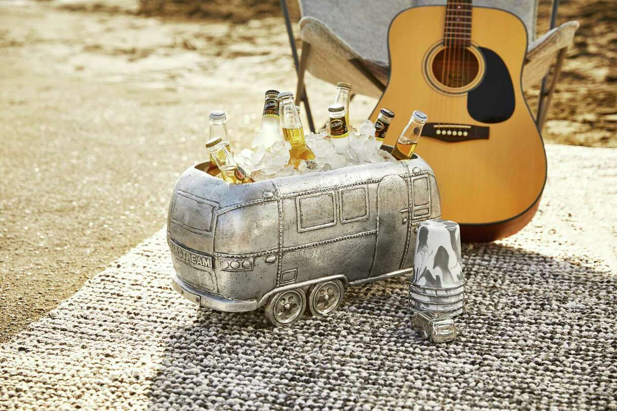 In a new collaboration with the RV company Airstream, Pottery Barn has launched a collection of gear that includes a fun drinks cooler shaped like the iconic trailer, shown here, as well as logo-embroidered napery and tumblers, bowls and plates in a snazzy grey and white enamelware swirl pattern. (Pottery Barn via AP)