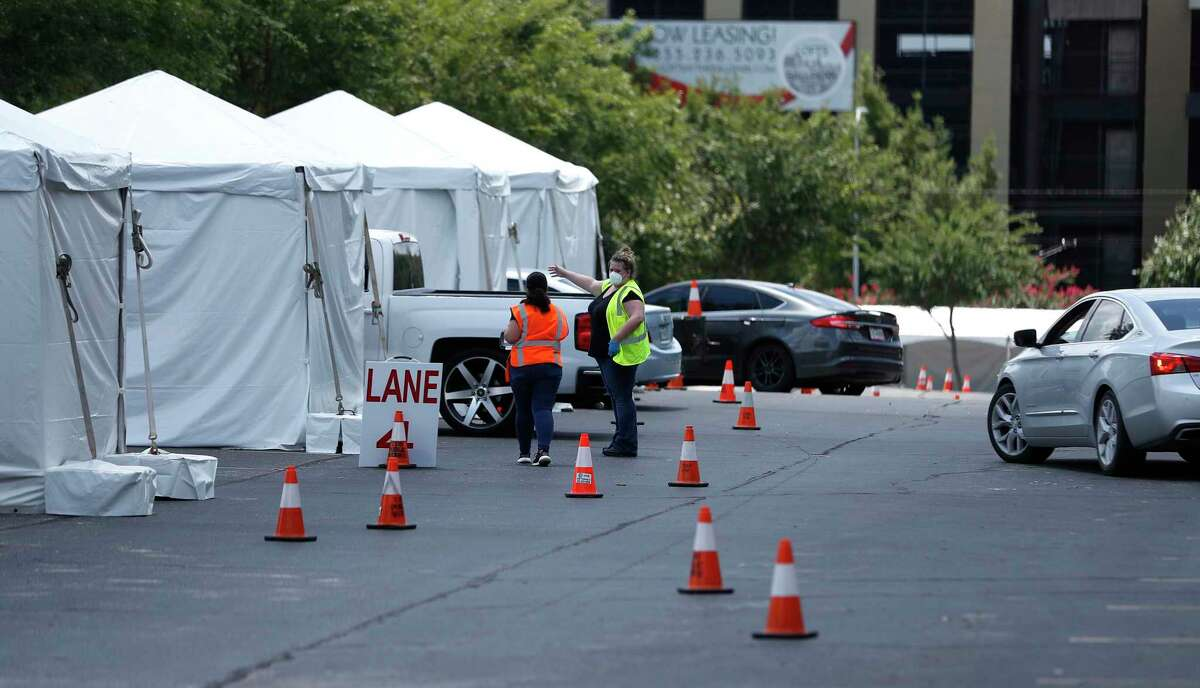 Women outside of tents as the Houston Astros opened up a Covid-19 testing site in parking Lot C, Saturday, August 8, 2020, in Houston. Located near Minute Maid Park, the testing site is capable of 2,000 tests a day. Testing will run 8 a.m. to 4 p.m., with eight drive-thru lanes and four walk-up lanes.