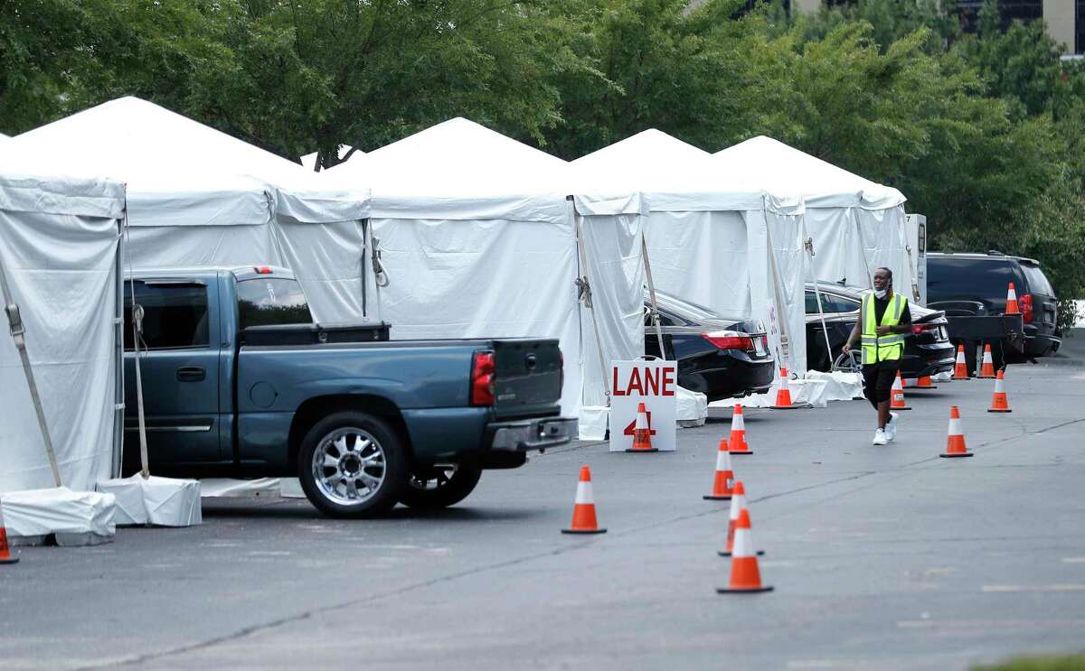 Cars line up next to tents as the Houston Astros opened up a Covid-19 testing site in parking Lot C, Saturday, August 8, 2020, in Houston. Located near Minute Maid Park, the testing site is capable of 2,000 tests a day. Testing will run 8 a.m. to 4 p.m., with eight drive-thru lanes and four walk-up lanes.