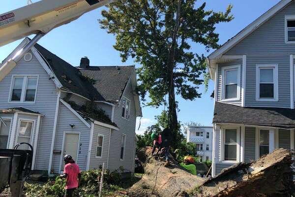 A tree down between homes on Beardsley Street in Bridgeport, Conn., on Saturday, Aug. 8, 2020.