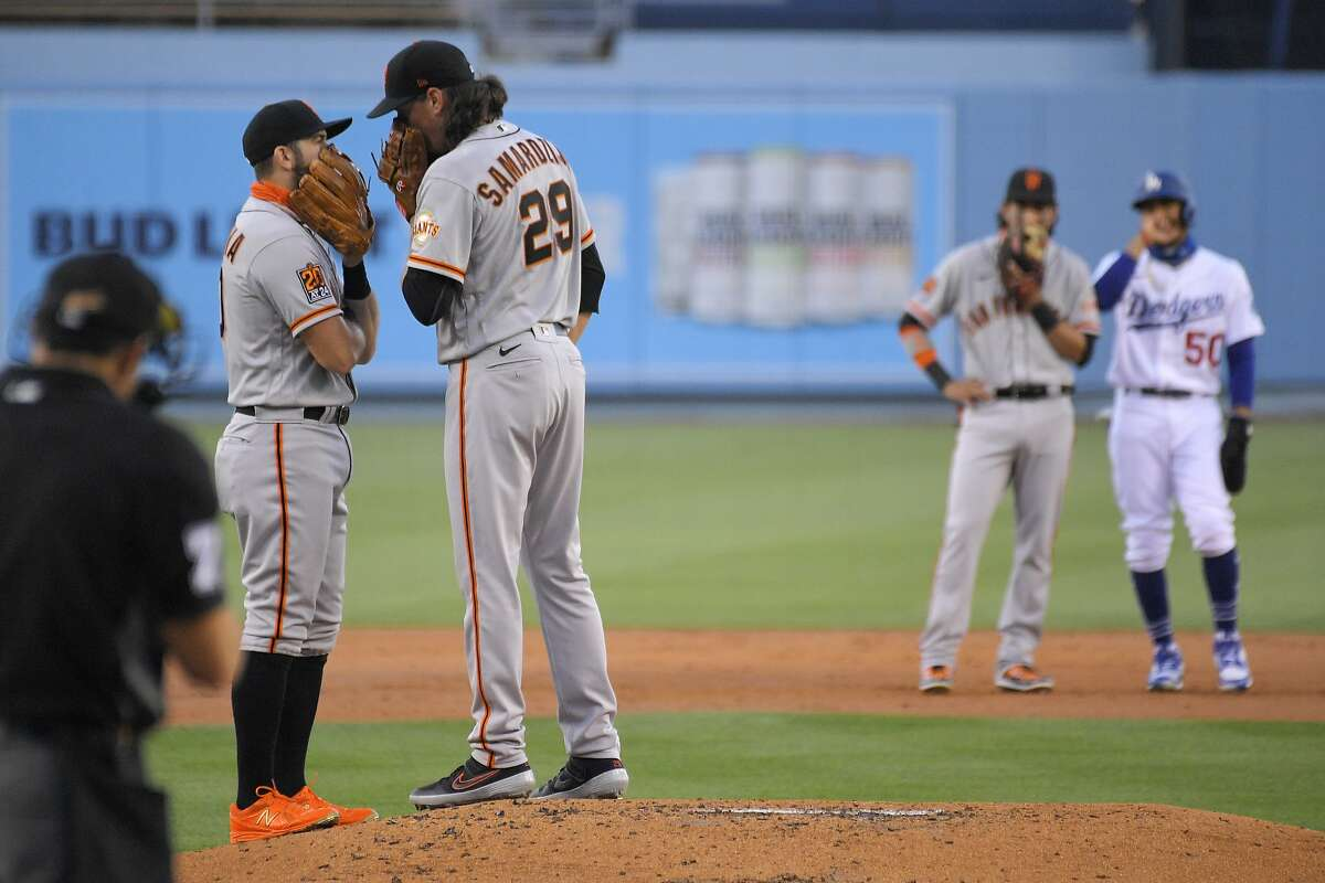 San Francisco Giants third baseman Evan Longoria, second from left, talks with starting pitcher Jeff Samardzija, center, as shortstop Mauricio Dubon, second from right talks with Mookie Betts during the first inning of a baseball game Friday, Aug. 7, 2020, in Los Angeles. (AP Photo/Mark J. Terrill)