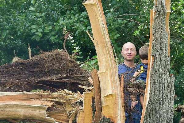 Tyler Maloney holds his one-year-old son Bear while being photographed with his three-year-old son Gage, at right, near a large tree in front of his home on Bertmor Drive in Stamford, Conn., on Aug., 8, 2020. The tree fell during Tropical Storm Isaias, cutting power and access to his neighborhood. Maloney and several of his neighbors are upset and concerned over the lack of response from both Eversource and city officials in clearing the tree and opening up the roadway.