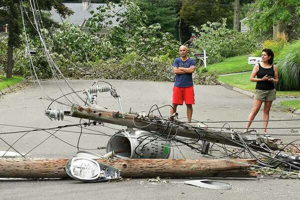 Neighbors of Bertmor Drive in Stamford, Conn., on Aug. 8, 2020, as they wait to have a fallen tree removed from the roadway and power restored to their neighborhood.