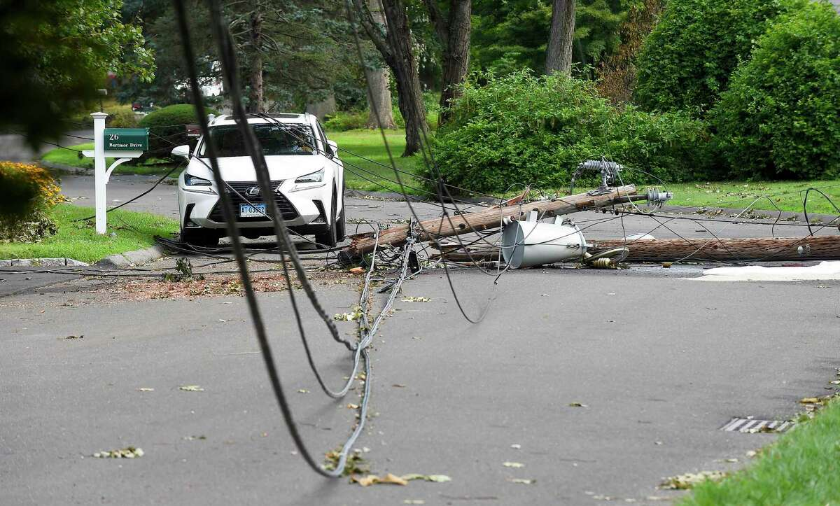Fallen powerlines lie atop a vehicle parked on Bertmor Drive in Stamford, Conn., on Aug. 8, 2020.